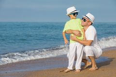 Father and son playing on the beach at the day time. Concept of. Father and son playing on the beach at the day time. People having fun outdoors. Concept of royalty free stock image