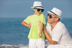 Father and son playing on the beach at the day time. Concept of. Father and son playing on the beach at the day time. People having fun outdoors. Concept of stock photos