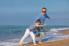 Father and son playing on the beach at the day time. Concept of. Father and son running on the beach at the day time. They are dressed in sailor`s vests. Concept Stock Photography
