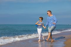 Father and son playing on the beach at the day time. Concept of. Father and son running on the beach at the day time. They are dressed in sailor`s vests. Concept stock photo