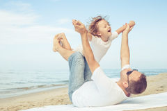 Father and son playing on the beach at the day time. Concept of friendly family Stock Photography