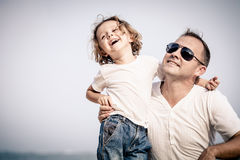 Father and son playing on the beach at the day time. Concept of friendly family Royalty Free Stock Photography