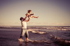 Father and son playing on the beach at the day time. Concept of. Father and son playing on the beach at the day time. People having fun outdoors. Concept of Royalty Free Stock Photo