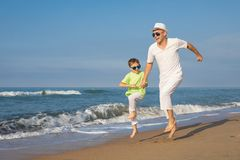 Father and son playing on the beach at the day time. Concept of. Father and son playing on the beach at the day time. People having fun outdoors. Concept of Royalty Free Stock Images