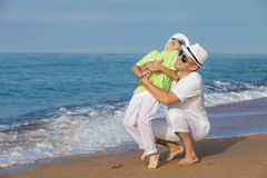 Father and son playing on the beach at the day time. Concept of. Father and son playing on the beach at the day time. People having fun outdoors. Concept of Stock Images