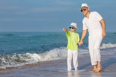 Father and son playing on the beach at the day time. Concept of. Father and son playing on the beach at the day time. People having fun outdoors. Concept of stock photo