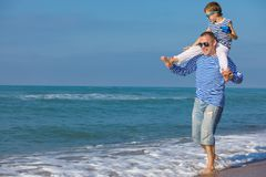 Father and son playing on the beach at the day time. Concept of. Father and son playing on the beach at the day time. They are dressed in sailor`s vests. Concept stock photos
