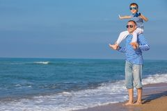 Father and son playing on the beach at the day time. Concept of. Father and son playing on the beach at the day time. They are dressed in sailor`s vests. Concept royalty free stock photo