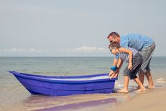 Father and son  playing on the beach at the day time. Father and  son playing on the beach at the day time. People having fun outdoors. Concept of summer Stock Images
