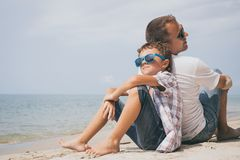 Father and son playing on the beach at the day time. Father and  son playing on the beach at the day time. People having fun outdoors. Concept of summer Royalty Free Stock Photography