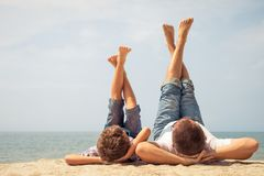 Father and son playing on the beach at the day time. Stock Images