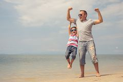 Father and son playing on the beach at the day time. Father and son playing on the beach at the summer day time. People having fun outdoors. Concept of summer royalty free stock image