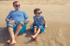 Father and son  playing on the beach at the day time. Father and  son playing on the beach at the day time. People having fun outdoors. Concept of summer Stock Photo