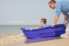 Father and son  playing on the beach at the day time. Father and  son playing on the beach at the day time. People having fun outdoors. Concept of summer Royalty Free Stock Photo