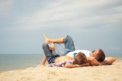 Father and son playing on the beach at the day time. Father and  son playing on the beach at the day time. People having fun outdoors. Concept of summer Stock Image