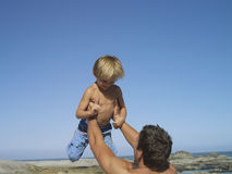 Father and son (4-6) playing on beach, man lifting boy above head Stock Photo