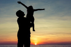 Father and son playing on the beach. At the sunset time. Concept of friendly family Royalty Free Stock Photos