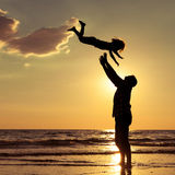 Father and son playing on the beach at the sunset time. Concept of friendly family Stock Images