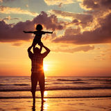 Father and son playing on the beach at the sunset time. Stock Photos