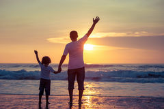Father and son playing on the beach at the sunset time. Royalty Free Stock Images