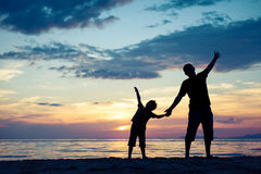 Father and son playing on the beach at the sunset time. Stock Photo