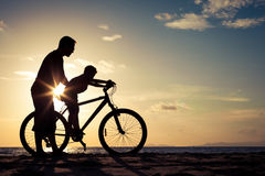 Father and son playing on the beach at the sunset time. Concept of happy friendly family Royalty Free Stock Images