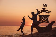 Father and son playing on the beach at the sunset time. They playing with a cardboard pirate ship. People having fun outdoors. Concept of summer vacation and royalty free stock images