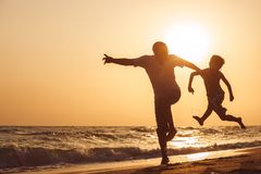 Father and son  playing on the beach at the sunset time. People having fun outdoors. Concept of summer vacation and friendly family Stock Photos