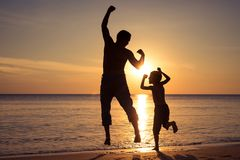 Father and son  playing on the beach at the sunset time stock images