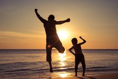 Father and son  playing on the beach at the sunset time royalty free stock image