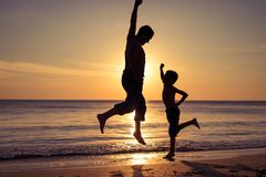 Father and son  playing on the beach at the sunset time royalty free stock images