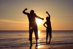 Father and son  playing on the beach at the sunset time royalty free stock photography