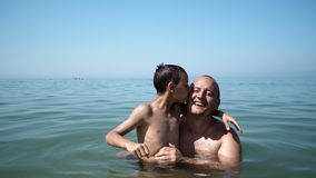 Father and son playing at beach together. Portrait fun happy lifestyle, boy embrace father kiss him stock images
