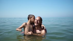 Father and son playing at beach together portrait fun happy lifestyle. Boy embrace father kiss him stock photography