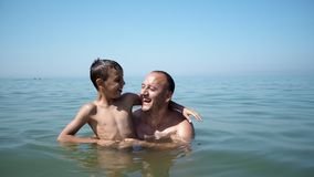 Father and son playing into the sea together. Father and son playing at beach together portrait fun happy lifestyle, boy embrace father and show victory stock image