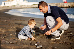 Father and son playing on the beach Stock Images