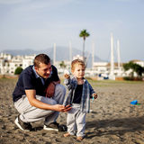 Father and son playing on the beach Stock Photo