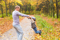 Father and son playing in a beautiful autumn park Royalty Free Stock Images