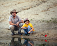 Father and son playing in the boats on the river bank, family va Stock Images
