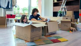 Father and son playing car racing with cardboard boxes. In the living room Stock Photos