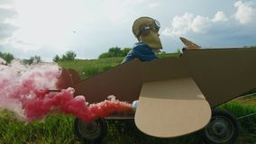 Father and son playing with cardboard airplane at the daytime. Little boy dressed in a cap and glasses aviator, flying in a cardboard airplane with attached stock video footage