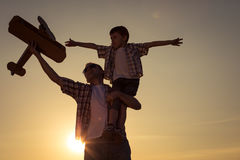 Father and son playing with cardboard toy airplane in the park a. T the sunset time. Concept of friendly family. People having fun outdoors Royalty Free Stock Photo