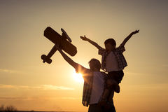 Father and son playing with cardboard toy airplane in the park a. T the sunset time. Concept of friendly family. People having fun outdoors Royalty Free Stock Image