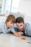 Father and son playing with cars on the floor Stock Photo