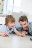 Father and son playing with cars on the floor Stock Images