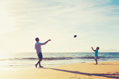 Father and Son Playing Catch Throwing Football. On the Beach at Sunset Stock Photo