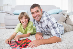 Father and son playing checker game on fur Stock Photos