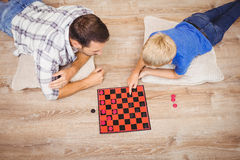 Father and son playing checker game while at home. High angle view of father and son playing checker game while lying on floor at home stock images