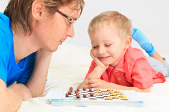 Father and son playing checkers Stock Photos
