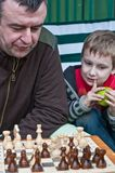 Father and son playing chess. Outdoors Stock Images
